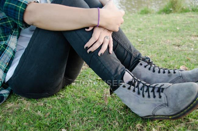 Cintura para baixo, jovem mulher sentada na grama — Fotografia de Stock