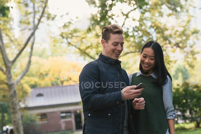 Средний взрослый пара в парке, чтение текстов смартфон — стоковое фото