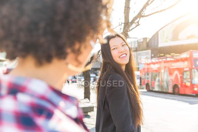 Vista sulla spalla della donna dai capelli lunghi nell'area urbana sorridendo ad un amico — Foto stock
