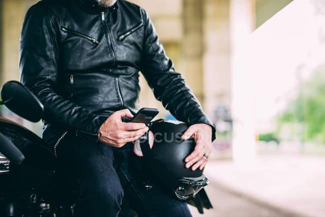 Seção intermediária do motociclista masculino maduro sentado em mensagens de texto de motocicleta no smartphone — Fotografia de Stock