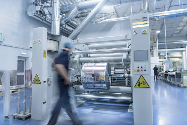 Blurred motion worker unloading printed roll in food packaging printing factory — Stock Photo