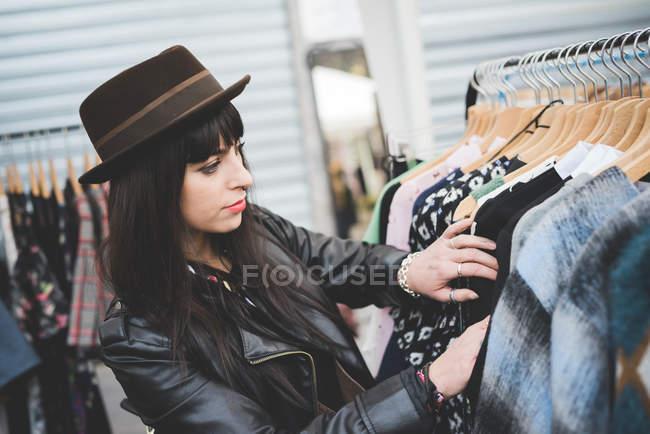 Joven viendo ropa en el mercado - foto de stock
