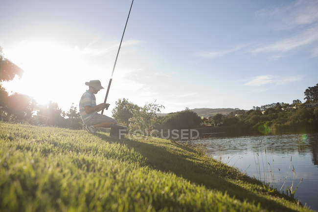 Mature man fishing on peaceful riverbank — Stock Photo