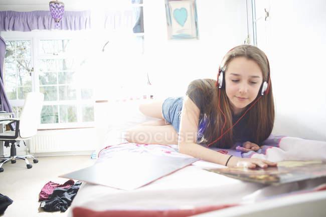 Девочка-подросток смотрит на обложку виниловой пластинки, слушая наушники в спальне — стоковое фото
