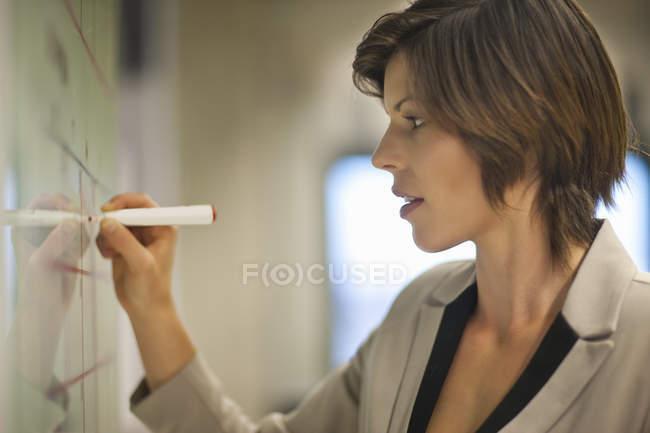 Junge geschäftsfrau, die Fahrpläne im Büro zu organisieren — Stockfoto