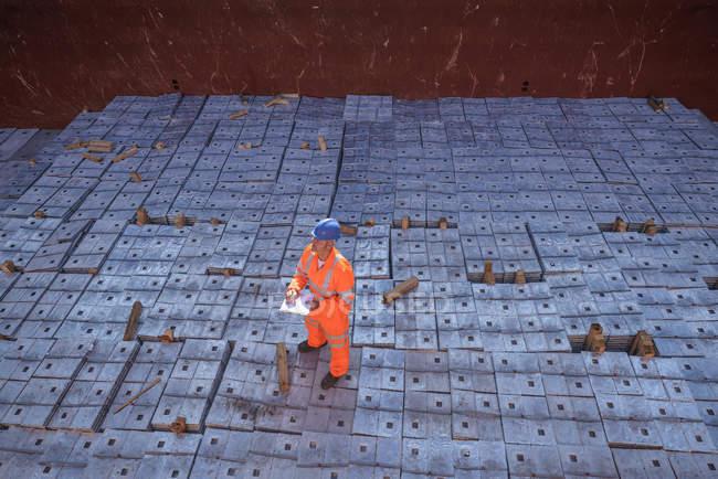 Trabalhador em vestuário de trabalho reflexivo em pé sobre carga de liga de metal no porão do navio — Fotografia de Stock