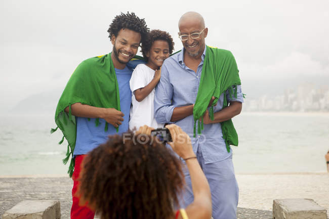 Over shoulder view of mother photographing family wrapped in Brazilian flag on Ipanema beach, Rio De Janeiro, Brazil — Stock Photo