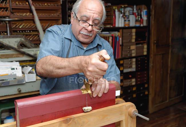 Старший чоловік застосування сусальне золото до книги хребта в традиційних палітурне майстерні — стокове фото