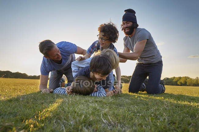 Family enjoying outdoor activity in park at sunset — Stock Photo
