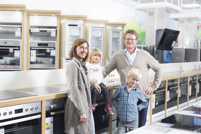 Portrait of family with two children browsing hobs in electronics store — Stock Photo