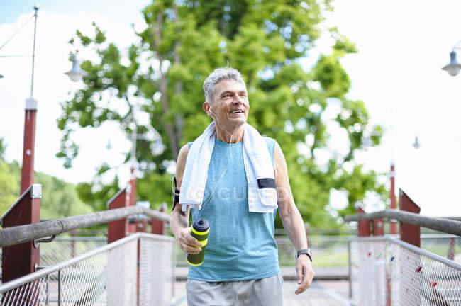 Senior male runner with water bottle crossing  footbridge — Stock Photo