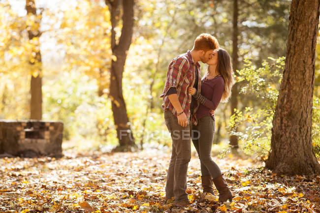 Jovem casal beijando na floresta de outono — Fotografia de Stock