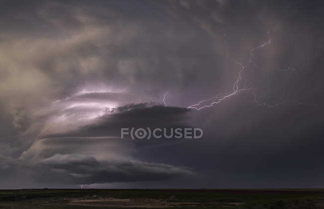 Ominous storm clouds with lightning above land — Stock Photo