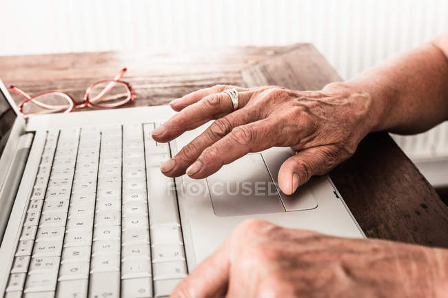 Older woman hands using laptop — Stock Photo