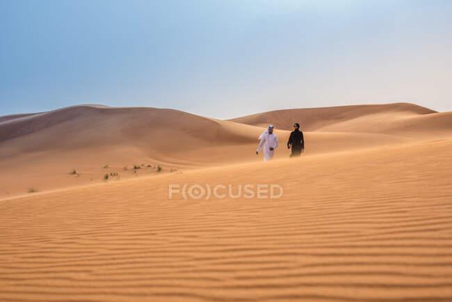 Віддалений вид на пару в традиційному одязі середнього сходу, що йде по пустелі дюн, Дубай, Об