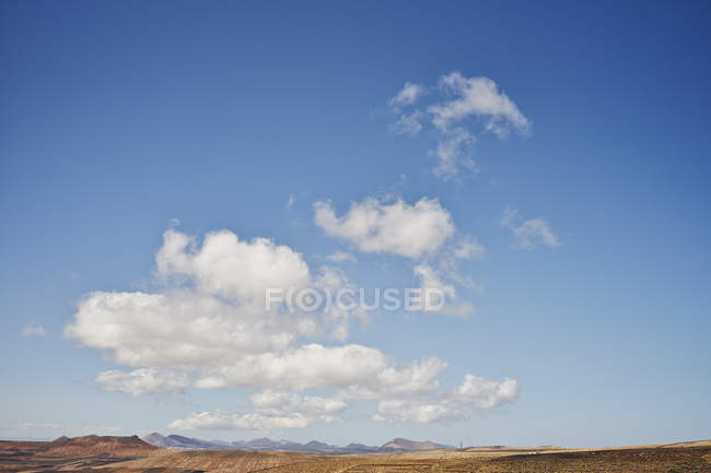 White clouds on blue sky above hilly landscape — Stock Photo