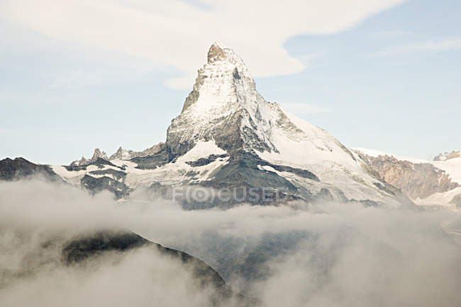 Snowcapped mountain peak and cloudy sky — Stock Photo