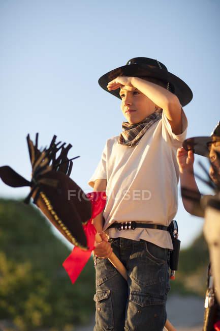 Due ragazzi vestiti da cowboy su cavalli da hobby — Foto stock