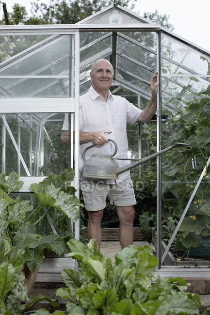 Portrait of senior man in garden greenhouse with watering can — Stock Photo