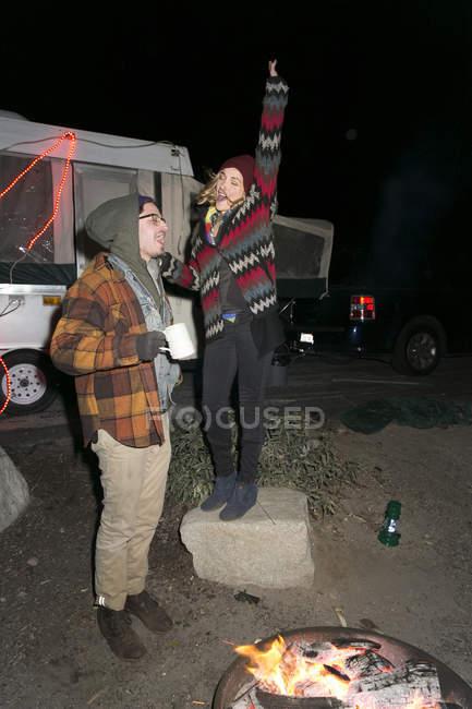 Jeune couple par le feu de camp, s'amuser — Photo de stock