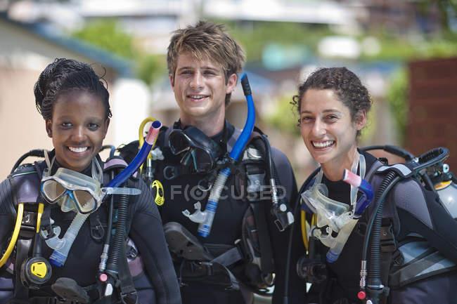 Портрет трех веселых молодых взрослых аквалангистов — стоковое фото