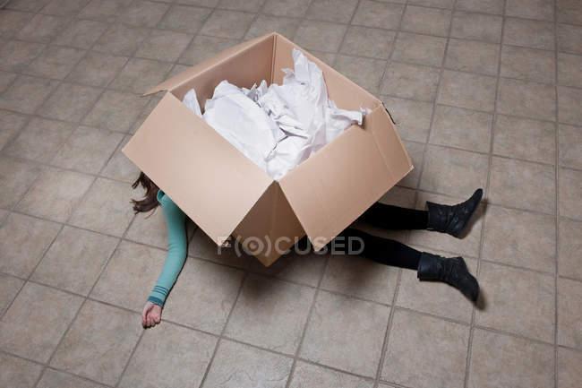 Vista de ángulo alto de la chica adolescente acostada debajo de la caja de cartón - foto de stock
