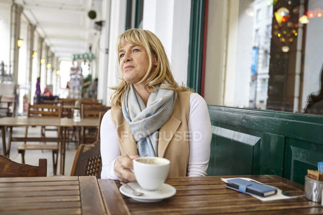 Femme mûre à l'affût de table café trottoir — Photo de stock