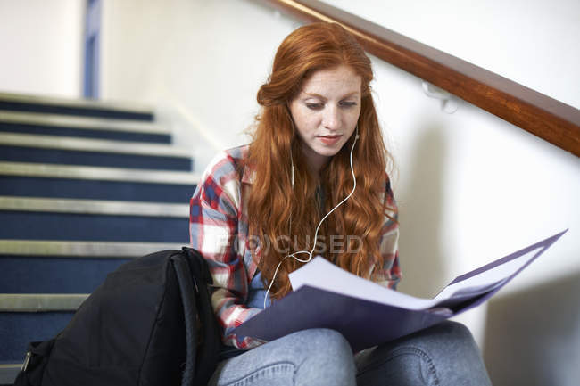 Young female college student sitting on stairway reading file — Stock Photo