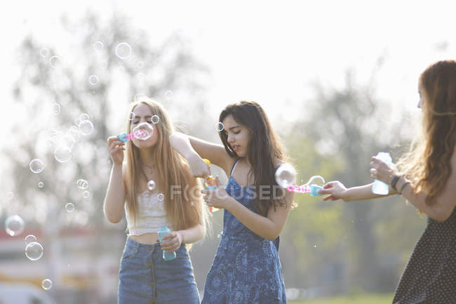 Three teenage girls blowing bubbles with bubble wand in park — Stock Photo