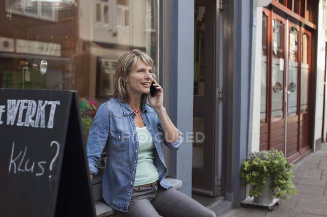Woman sitting on shop windowsill making telephone call — Stock Photo