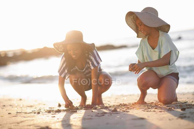 Женщины рисуют на песке на пляже — стоковое фото