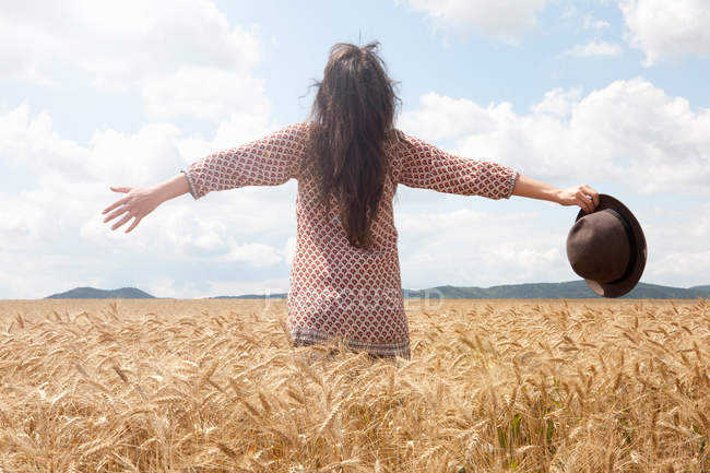 Mid adult woman standing in wheat field with arms out wide — Stock Photo