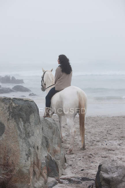 Woman riding horse on beach — Stock Photo