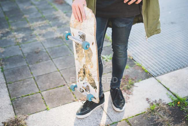 Taille vers le bas de la vue du jeune skateur urbain mâle debout sur le trottoir — Photo de stock