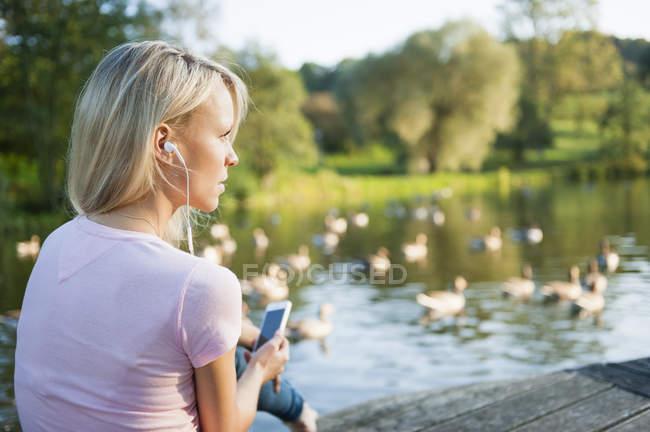 Joven mujer vestida con auriculares - foto de stock