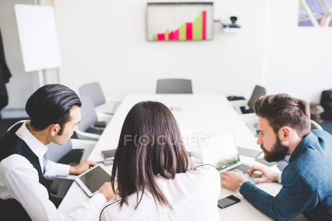 Бизнесмены и женщины встречаются за столом в зале заседаний — стоковое фото