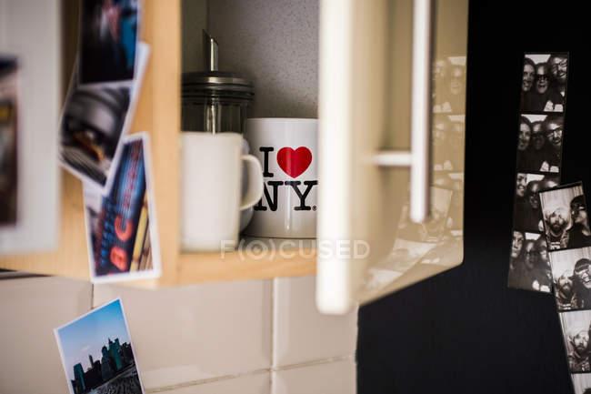 Сахарная чашка и чашки в открытом кухонном шкафу — стоковое фото