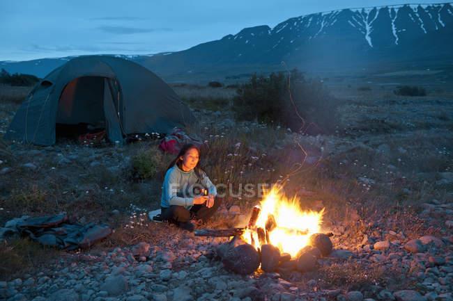 Donna seduta al falò, Eyjafjordur, Nord Islanda — Foto stock