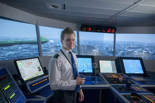 Retrato de estudante segurando rádio de comunicação na sala de simulação da ponte do navio — Fotografia de Stock