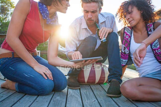 Jovens mulheres e homens usando tablet digital no convés — Fotografia de Stock