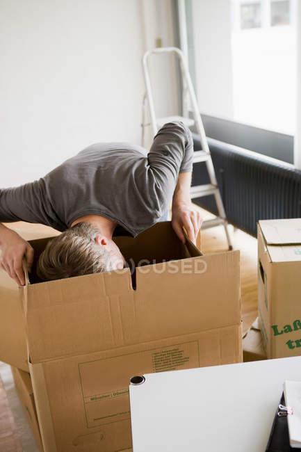 Homme recherchant des boîtes en carton — Photo de stock