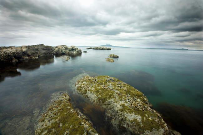 Rocce ricoperte di muschio sulla costa con cielo nuvoloso — Foto stock