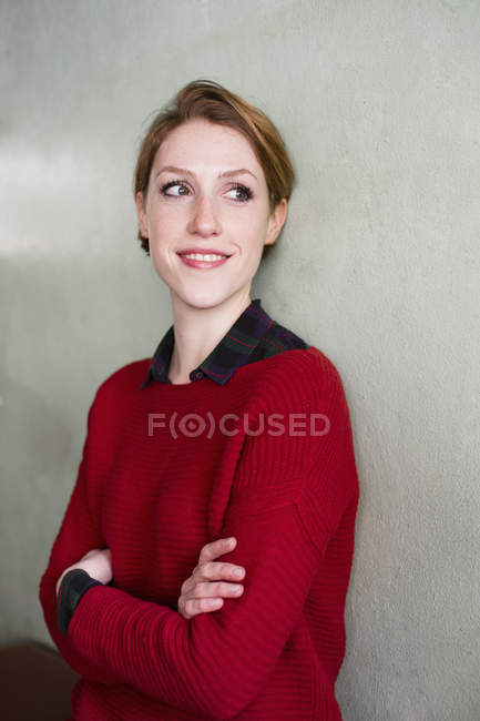 Close-up of young redhead woman with arms crossed — Stock Photo