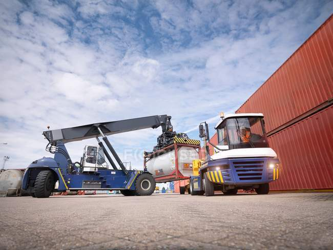 Укладка кранов контейнеров-цистерн из грузовика в порту — стоковое фото