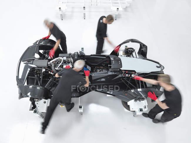 Coordenadores que montam o supercarro na fábrica do carro de esportes, vista aérea — Fotografia de Stock