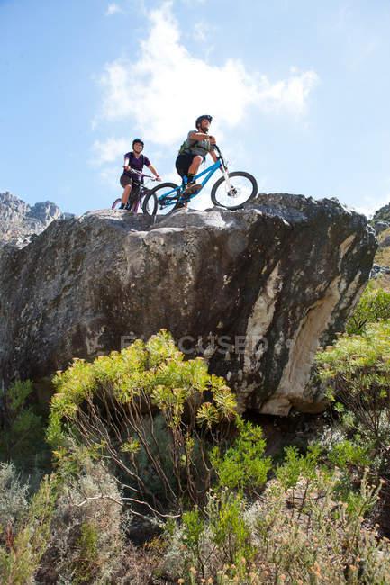 Young couple on mountain bikes looking at view — Stock Photo