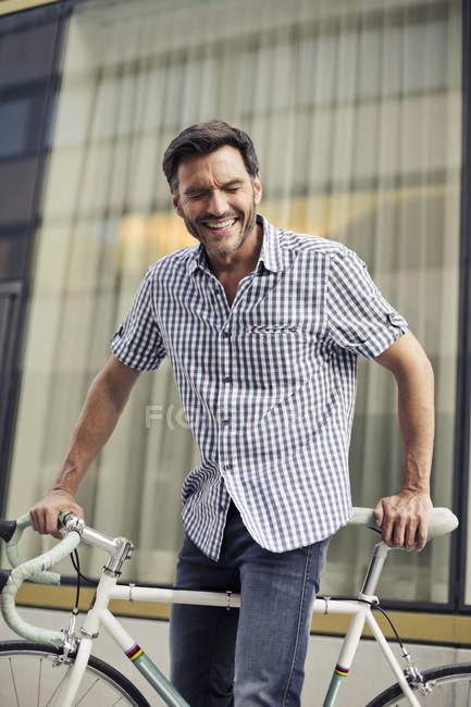 Maduro ciclista masculino rindo na rua da cidade — Fotografia de Stock