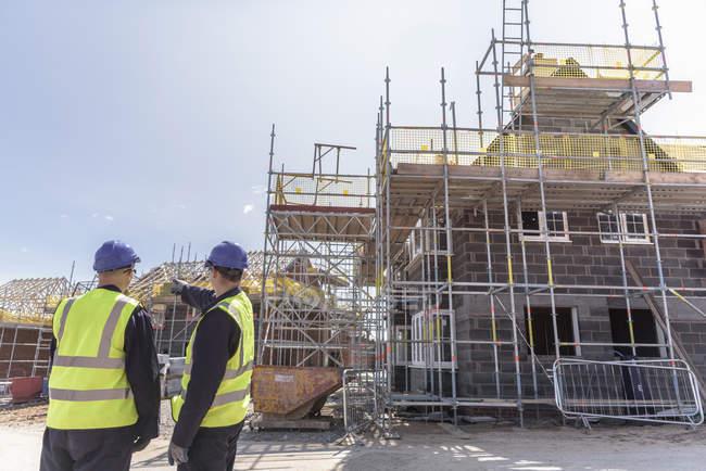 Bâtisseurs discutant du développement résidentiel sur le chantier — Photo de stock