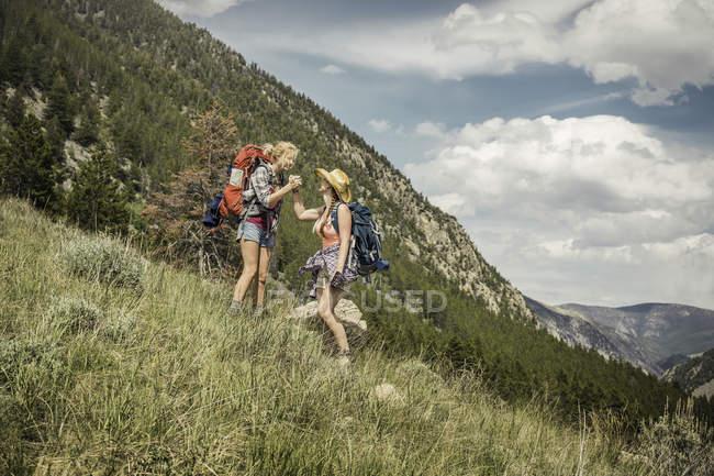 Adolescente y joven excursionista mujer estrechándole la mano en la ladera de la montaña, Red Lodge, Montana, Usa - foto de stock