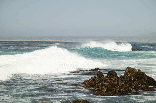Vagues frappant des rochers sur le rivage nuageux — Photo de stock